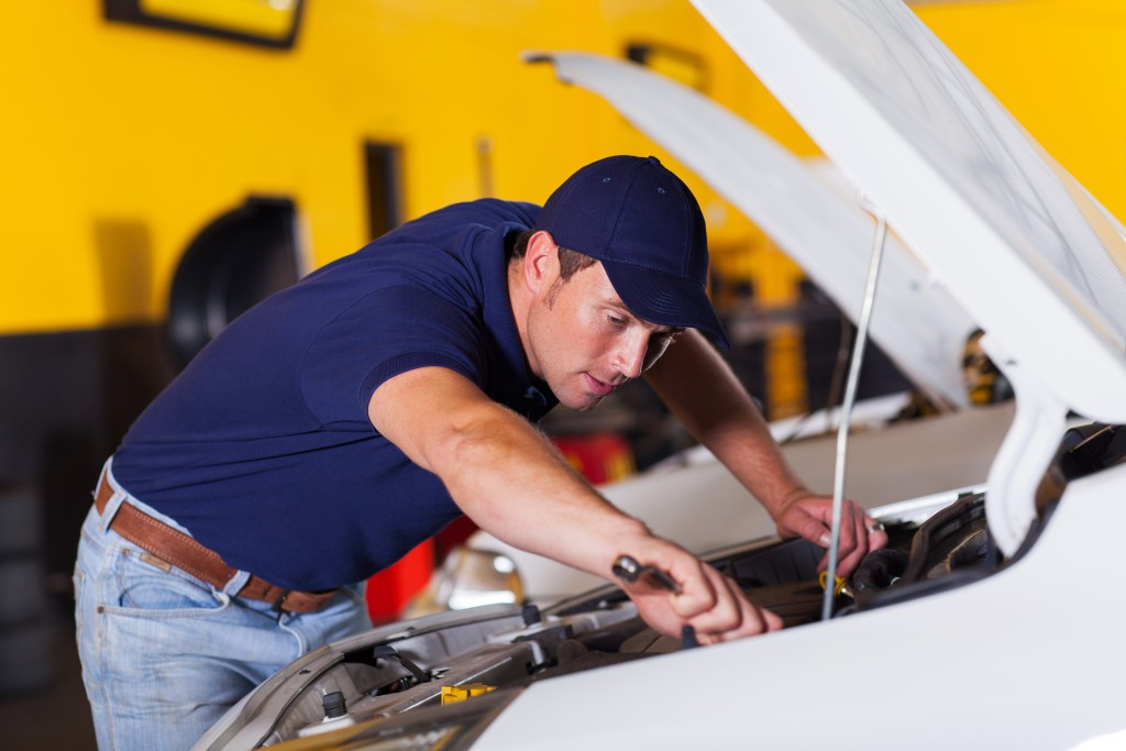 Auto mechanic repairing a white car