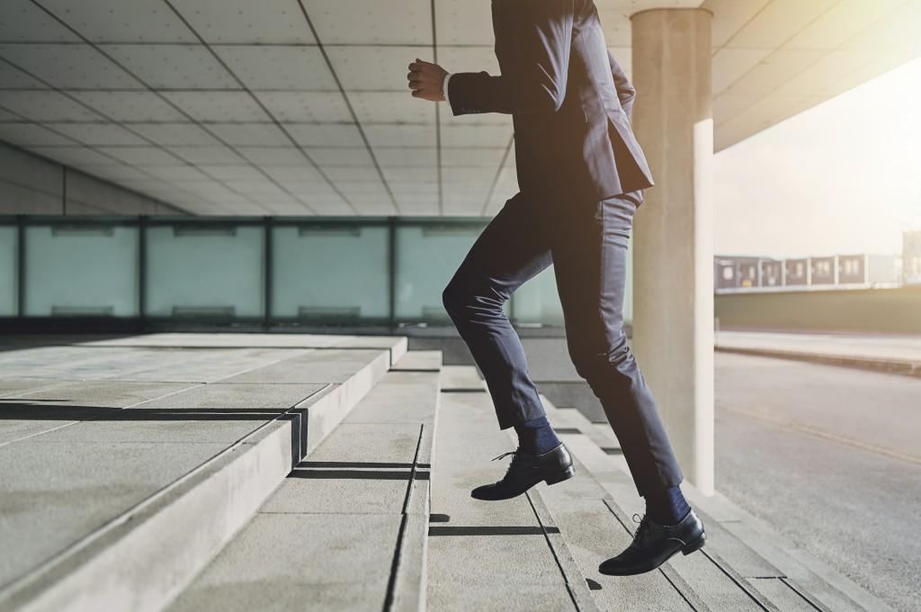 businessman climbing steps, wealth concept