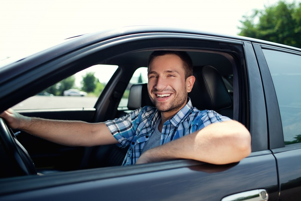 Man smiling in his car