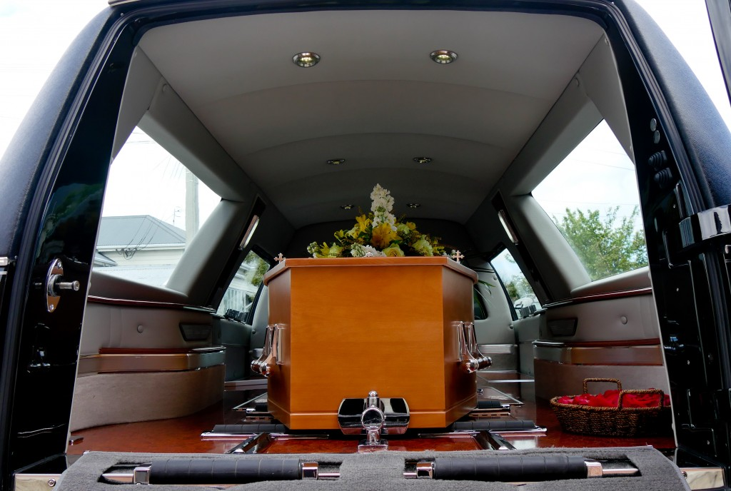 Wooden casket inside a funeral car