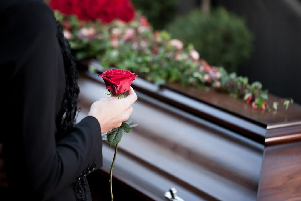 woman holding a rose near a coffin