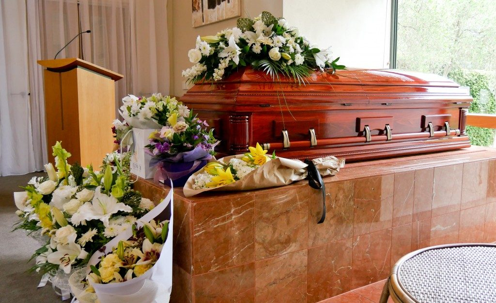 bouquet of flowers near a coffin