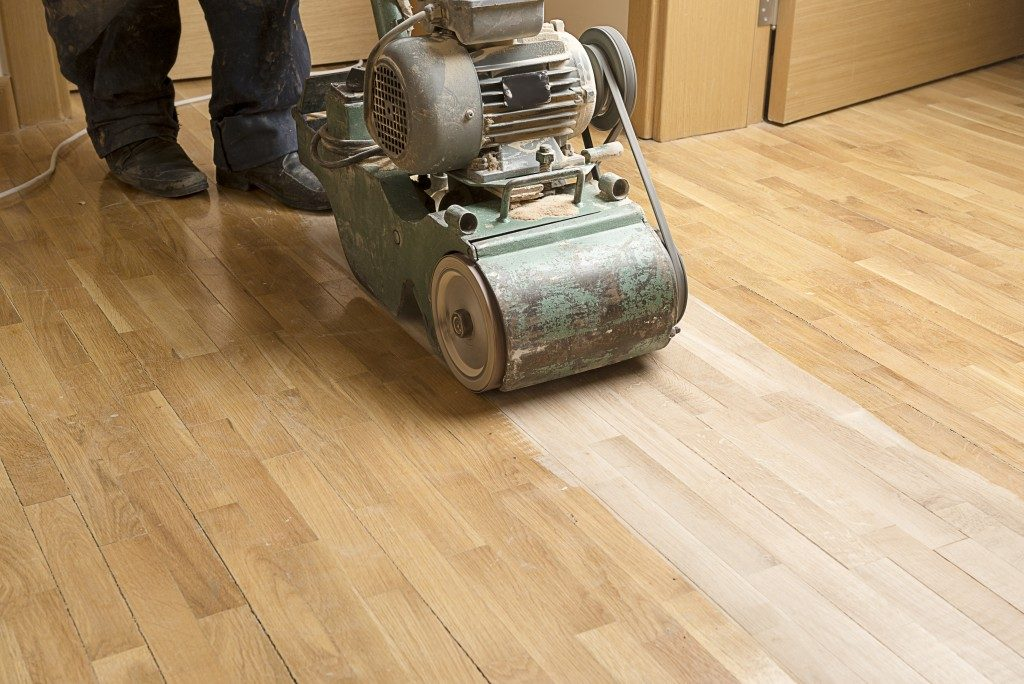 Wood floor polishing maintenance work by grinding machine.