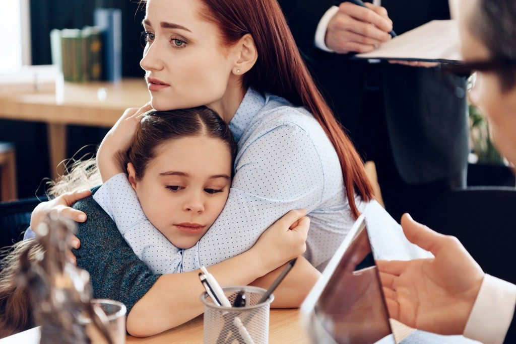 Little girl hugging mom with lawyer