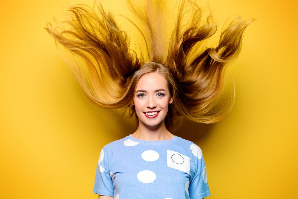 woman bouncing her healthy hair in a yellow background