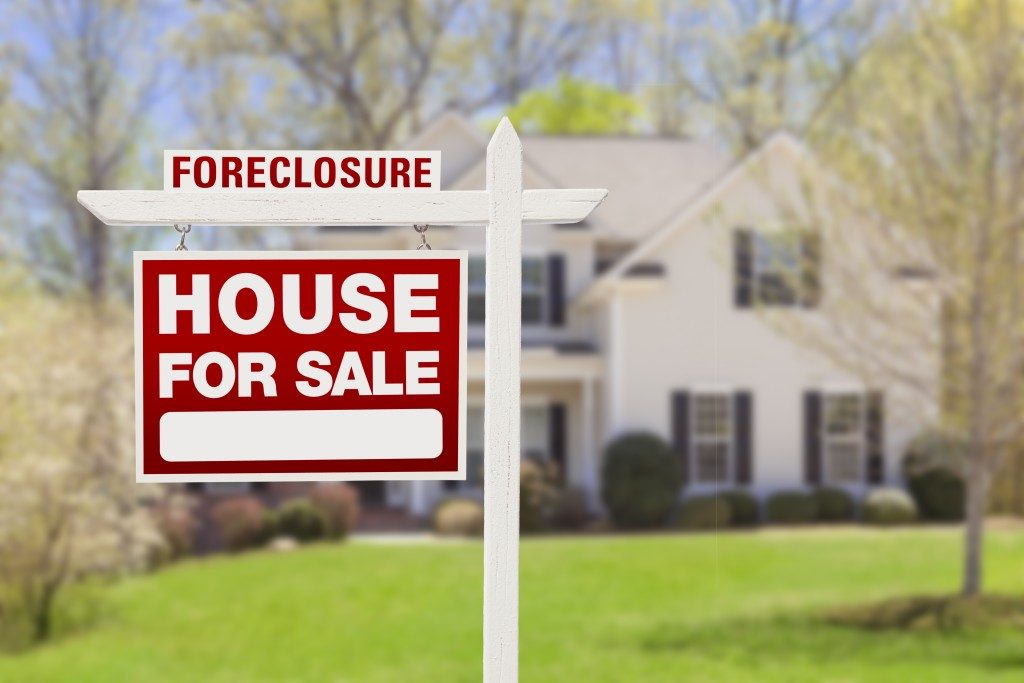 Red Foreclosure Home For Sale Real Estate Sign in Front of House
