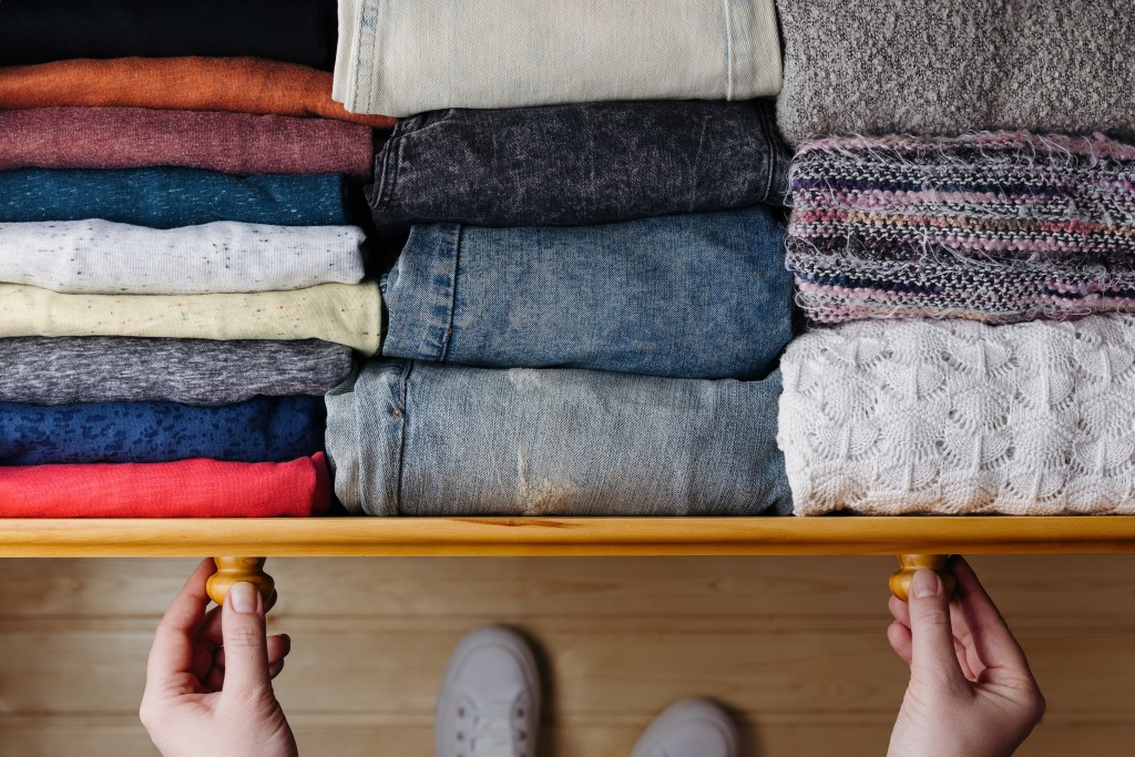 Overhead shot of neatly ordered clothes in wooden drawer