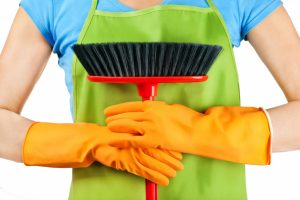woman holding a cleaning brush with yellow rubber gloves on