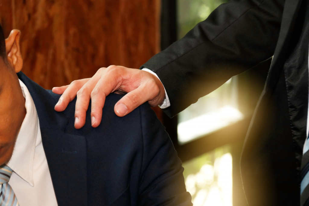 A man tapping co-worker's shoulder