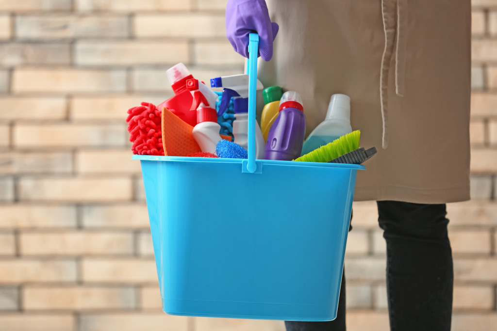 person holding cleaning supplies