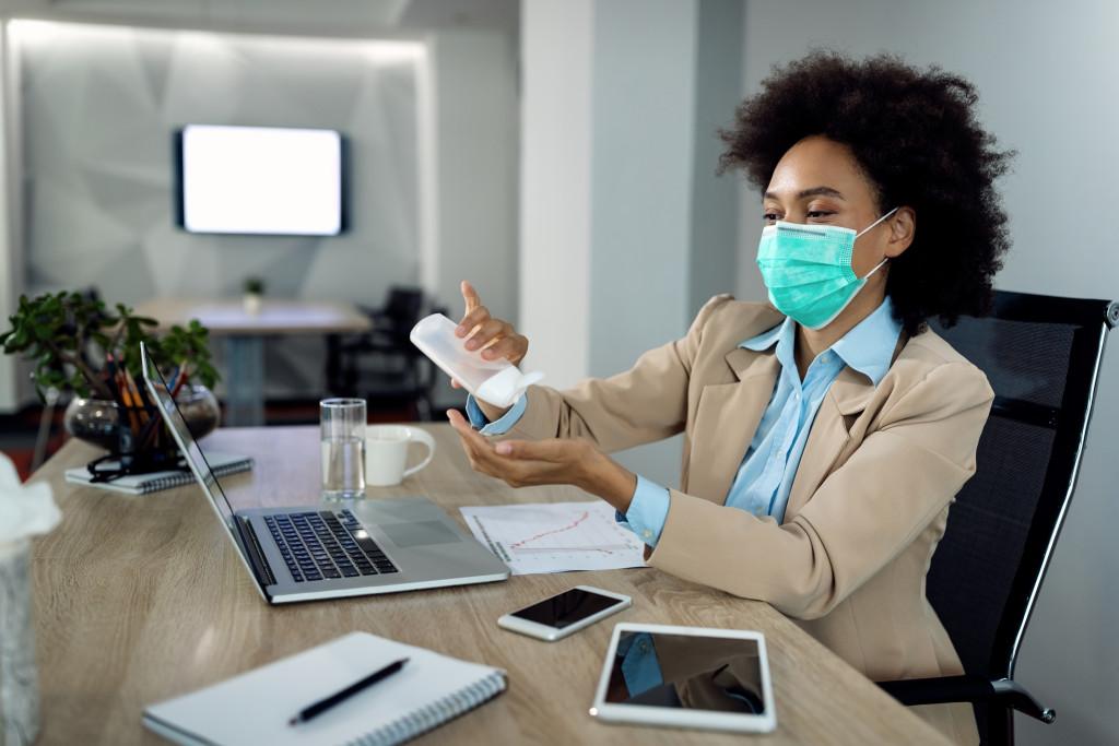 woman applying hand sanitizer wearing facemask